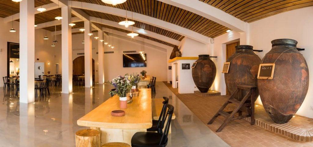 Sala da Casa das Talhas para refeições e eventos. Mesas, cadeiras e bancos em madeira. Três talhas antigas.