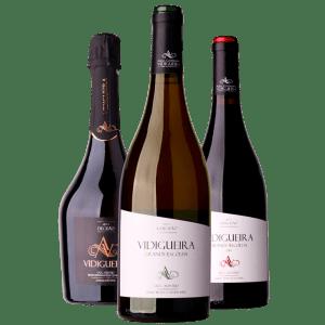 Três garrafas de vinho. Em primeiro plano Vidigueira Grande Escolha Branco e em segundo plano Vidigueira Grande Escolha Tinto e Espumante Vidigueira DOC. Vinhos e espumante da Adega Cooperativa Cuba e Alvito