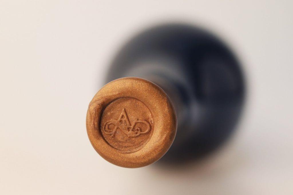 Vista de cima do invólucro da capsula de uma garrafa de vinho com o logo da Adega Cooperativa Vidigueira, Cuba e Alvito